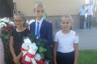 dzieci z wiązanką kwiatów