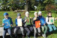 chłopcy siedzą i trzymają kartki z napisem jesień