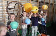 Dzieci trzymają planety nad głowami