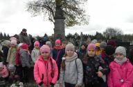 Dzieci pozują do zdjęcia obok pomnika