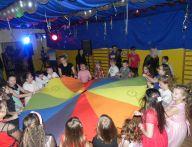 dzieci machają kolorową płachtą cd.