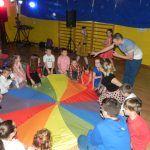 dzieci bawią się ze kolorowym spadochronem