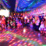 młodzież siedzi pod oknami gdy dzieci tańczą