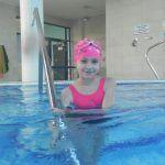 dziecko siedzi na schodkach basenu