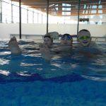 dzieci pływają na plecach